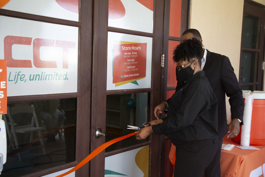 Sales Rep Denise Stevens cuts ribbon with Jamalie Thomas